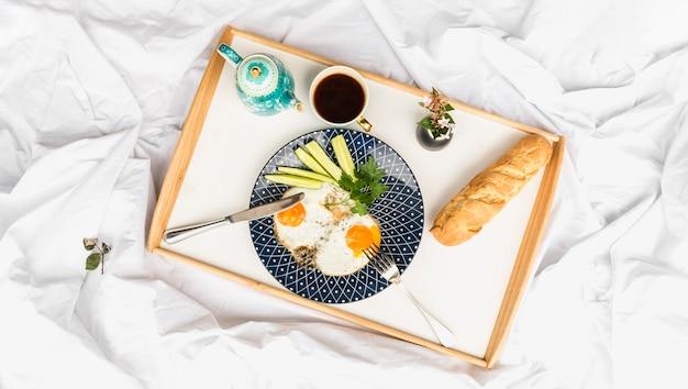 Omelete de ovo frito com pão e chá na bandeja de madeira sobre a cama