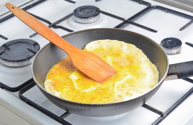 Omelete de ovo frito de ovos de galinha em uma frigideira no fogão