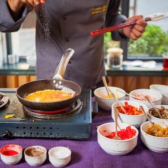 Omelete de vista lateral em uma panela homem cozinha uma omelete em uma panela com legumes, especiarias