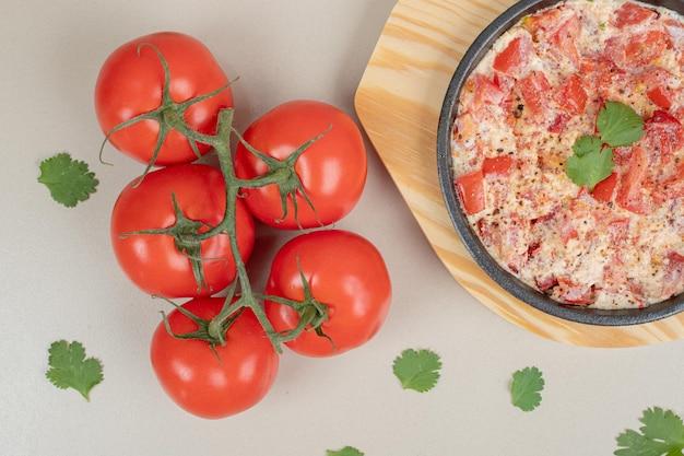 Omelete delicioso com tomate na placa de madeira.