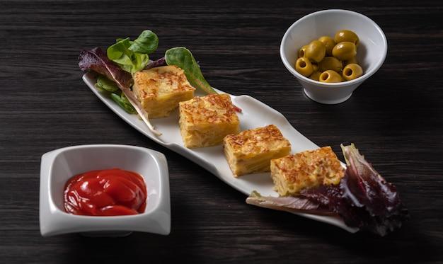 Omelete espanhol e azeitonas no restaurante