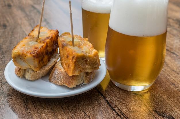 Omelete espanhola e dois copos de cerveja em uma mesa de madeira