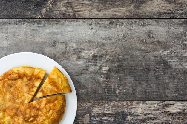 Omelete espanhola tradicional e garfo na mesa de madeira copyspace