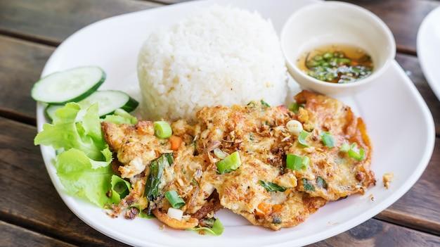 Omelete (estilo tailandês) com arroz em um prato branco.