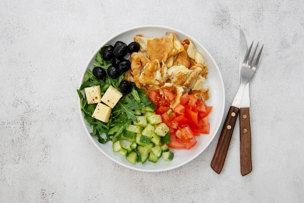 Omelete fresca com legumes frescos, foguete de salada, tomate, pepino, azeitonas, queijo. vista do topo.