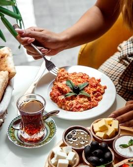 Omelete frito com tomate e chá preto