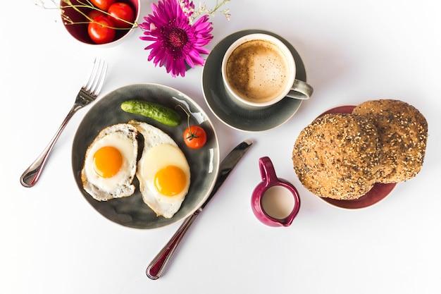 Omelete frito, pão com chá no pano de fundo branco