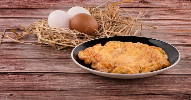 Omelete na mesa de madeira e ovos