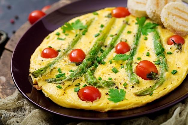 Omelete (omelete) com tomate, espargos e cebola verde na placa.