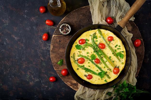 Omelete (omelete) com tomate, espargos e cebolinha na panela.