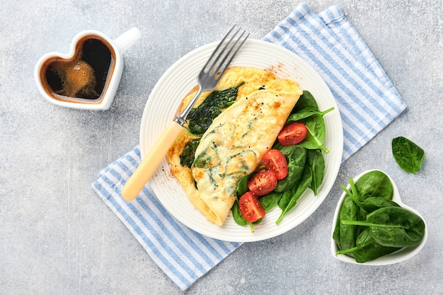 Omelete ou omelete com espinafre, tomate cereja e tempero de pimenta em prato branco,
