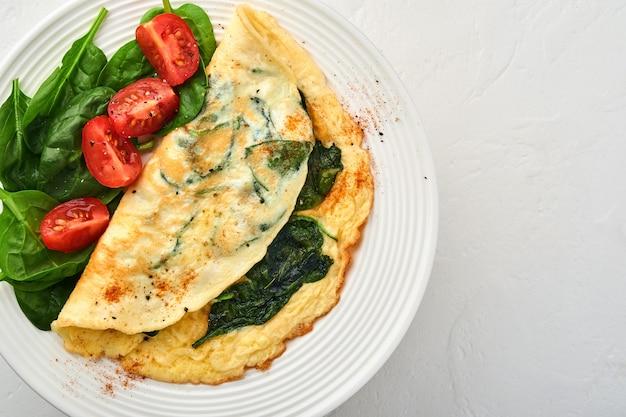 Omelete ou omelete com espinafre, tomate cereja e tempero de pimenta em prato branco