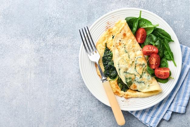 Omelete ou omelete com espinafre, tomate cereja e tempero de pimenta