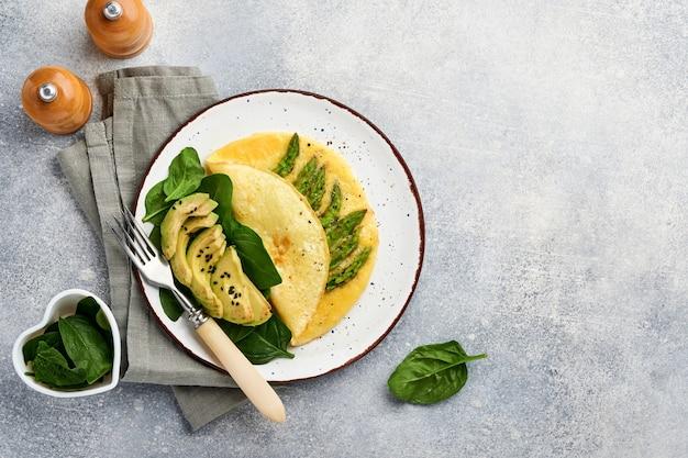 Omelete ou omelete recheado com aspargos, folhas de abacate e espinafre no café da manhã em prato branco