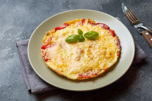 Omelete, ovos mexidos com tomate e queijo em um prato sobre uma mesa escura.