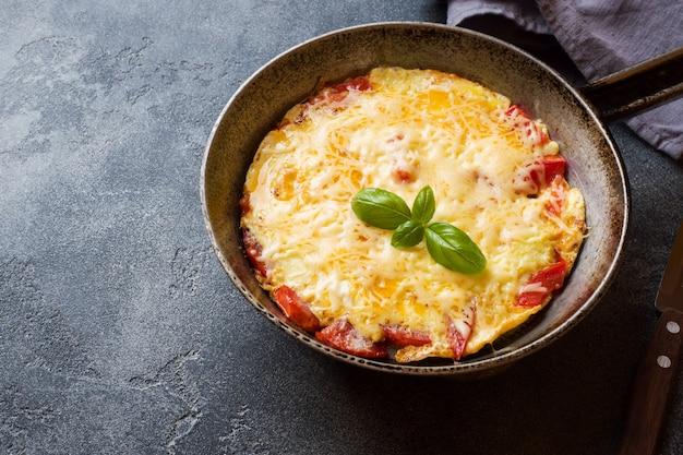 Omelete, ovos mexidos com tomate e queijo em uma panela sobre uma mesa escura.