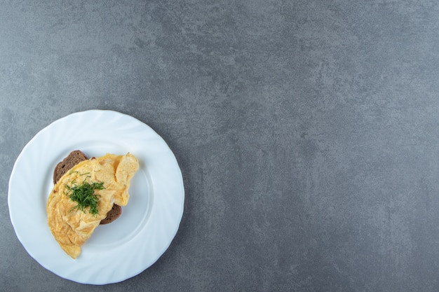 Omelete saboroso com pão na chapa branca.