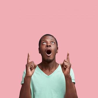 Omg e conceito de choque. homem afro-americano surpreso indica no espaço da cópia em branco upwads com os dedos da frente, isolados sobre a parede rosa