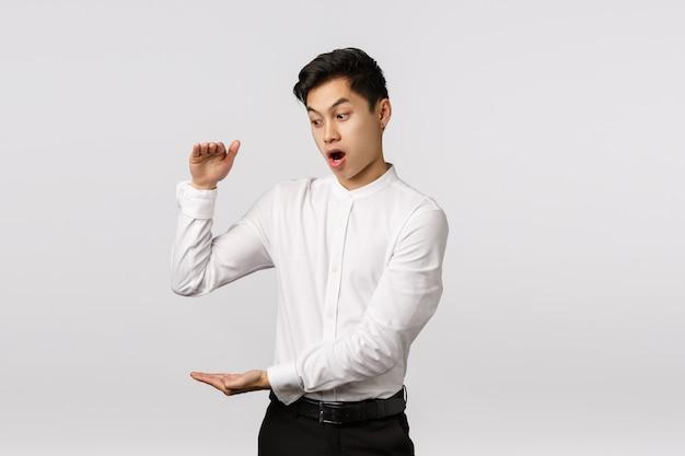 Omg empresário chocado com o quão rápido as finanças aumentam. surpreendido e impressionado, animado empregado masculino asiático ficando rico rapidamente, mostrando algo grande, moldando uma caixa grande