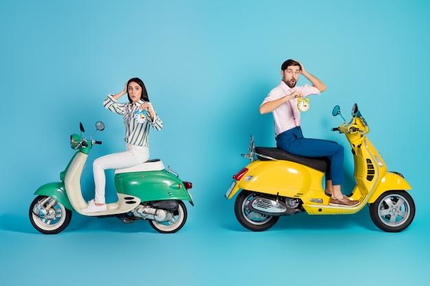 Omg, estamos atrasados! foto lateral de perfil de corpo inteiro de esposa chocada e espantada marido andar de scooter, olhar, eles perdem o tempo tocar a cabeça mãos impressionadas em velocidade lenta isolada parede azul