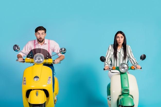 Omg inacreditável! esposa louca e atônita, marido dirigir moto, olhar incrível propaganda gritar uau, usar camisa formal rosa listrada isolada sobre parede de cor azul