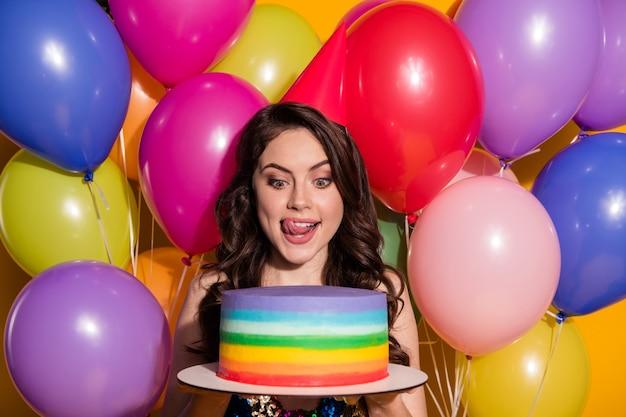 Omg, vamos comer o bolo inteiro. menina animada positiva comemorar evento de aniversário segurar pastelaria de aniversário olhar lamber lábios usar lantejoulas vestido isolado com fundo de cor de brilho brilhante de balões