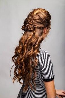 Onda cachos penteado. penteado na mulher de cabelo castanho vermelho com cabelos longos em fundo cinza. serviços profissionais de cabeleireiro. estilo de cabelo, trança com gancho de cabelo.