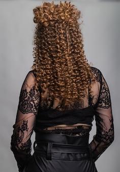 Onda cachos penteado. penteado na mulher de cabelo castanho vermelho com cabelos longos em fundo cinza. serviços profissionais de cabeleireiro