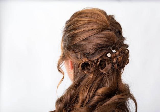 Onda cachos penteado. penteado na mulher de cabelo castanho vermelho com cabelos longos, sobre um fundo branco. serviços profissionais de cabeleireiro. estilo de cabelo, trança com gancho de cabelo.