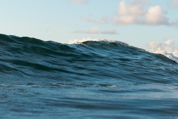 Onda clara do oceano com céu e nuvens