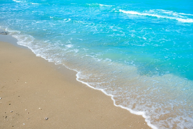 Onda de água azul na areia da praia