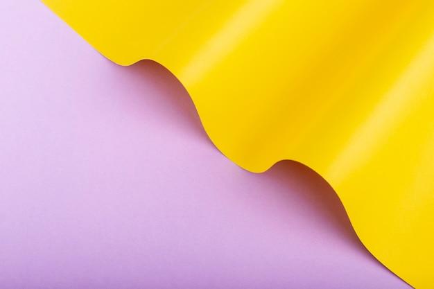 Onda de papelão amarelo sobre fundo lilás. vista superior, configuração plana.