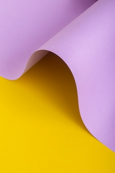 Onda de papelão lilás sobre fundo amarelo. vista superior, configuração plana.