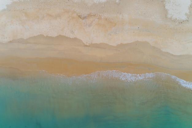 Onda do mar da praia tropical vista superior aérea espirrando na espuma do mar branco da costa arenosa.