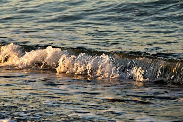 Onda do mar de verão ao pôr do sol