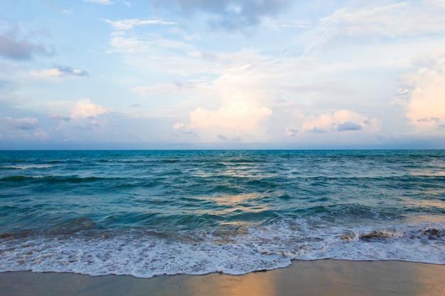 Onda do mar na praia de areia e lindo céu