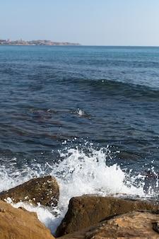 Onda do mar quebrando grande em uma praia arenosa