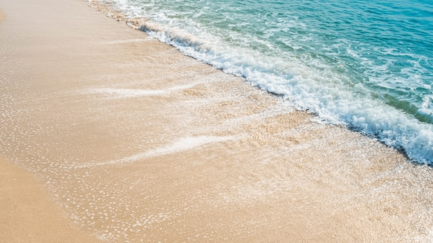 Onda do oceano azul na praia de areia. textura de fundo.
