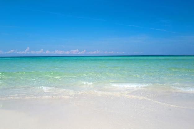 Onda do oceano azul suave na bela praia de areia limpa com lagoa de água do mar azul e areia branca ...