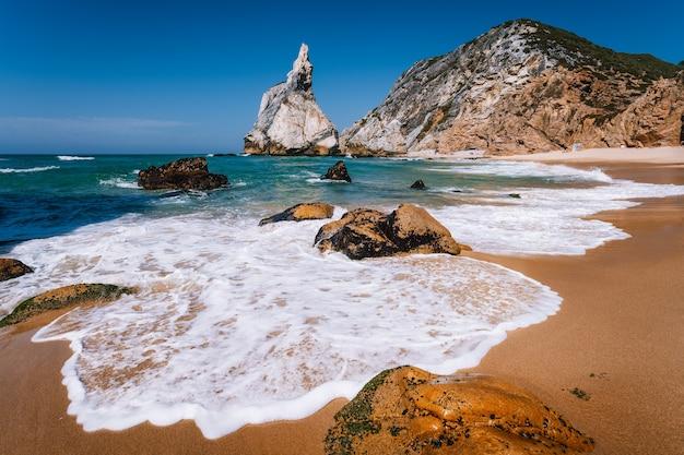 Onda espumosa na praia de areia com rochas surreais na praia de ursa, portugal
