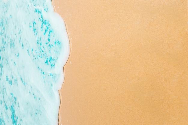 Onda macia do oceano azul na praia arenosa.