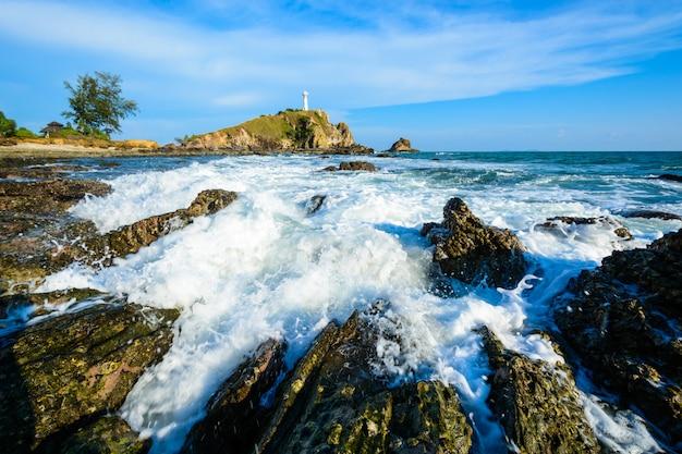 Onda na praia da rocha com farol na ilha de lanta, tailândia