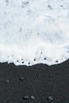 Onda oceânica com espuma branca rola sobre praia de areia preta com seixo. costa de areia vulcânica de tenerife.