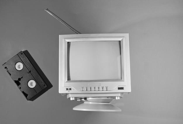 Onda retro, conceito dos anos 80 de minimalismo. retro tv com antena, videocassete. foto em preto e branco. vista do topo