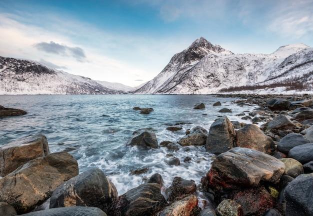 Onda seascape batendo rochas com montanhas no litoral ártico