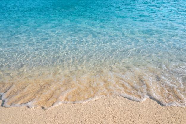 Onda suave rodou o fundo da praia arenosa