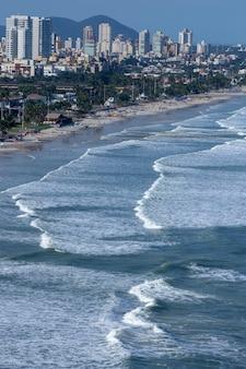 Ondas atingindo a praia com cidade ao fundo