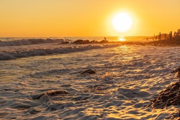 Ondas azuis escuras contra o belo pôr do sol laranja no mar negro, anapa, rússia