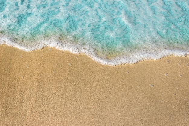Ondas azuis macias com espuma do oceano no fundo da praia arenosa.