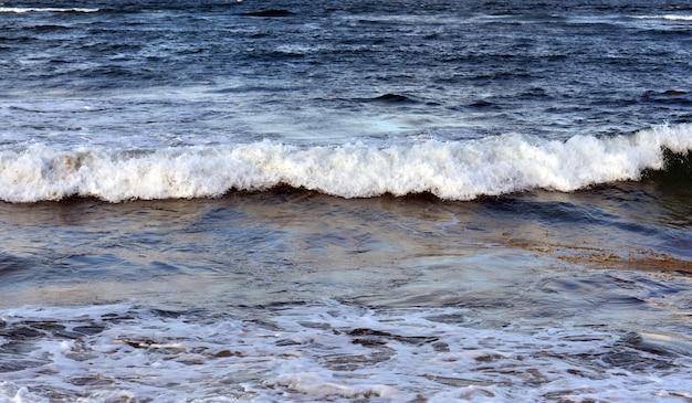 Ondas brancas rolam para a costa